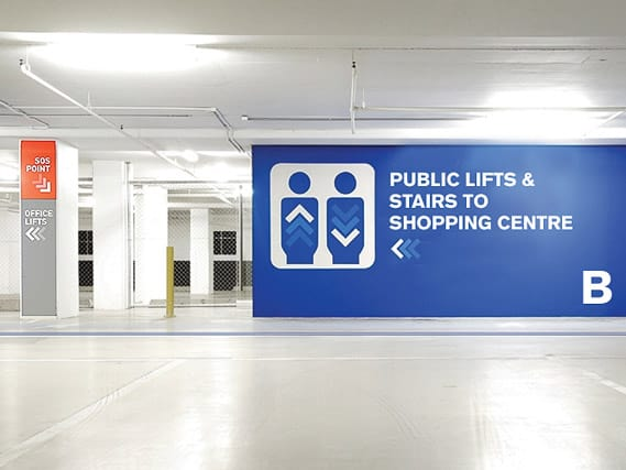 A digital printed wall graphic used as directional signage in a car park