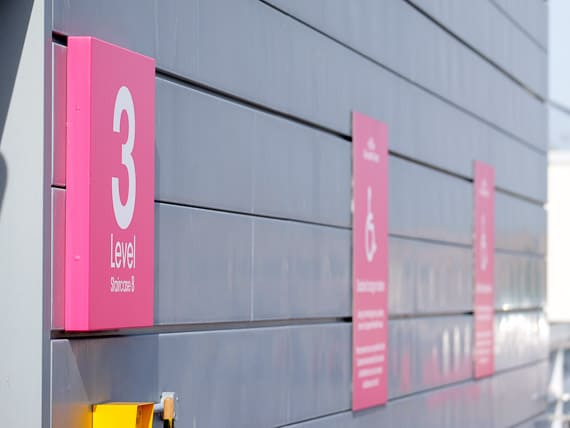 Folded aluminium trays with edge wrapped printed graphics used as directional signage