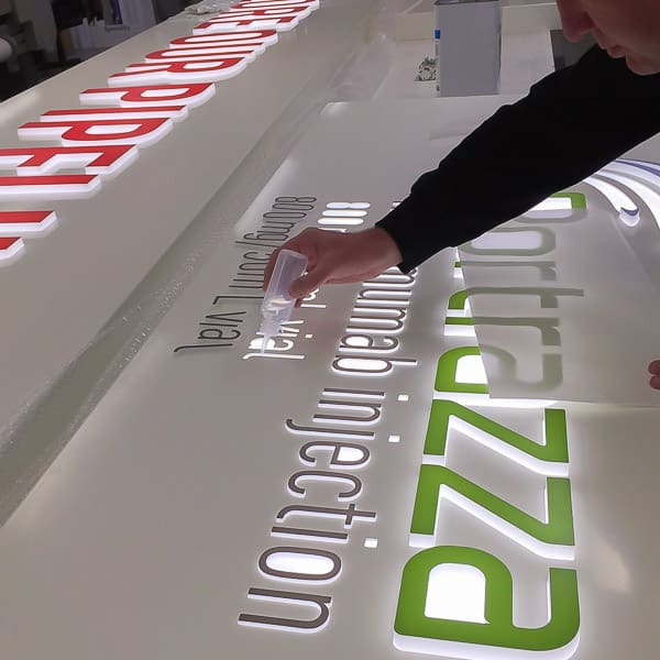 Acrylic letters with vinyl faces being glued into a routed aluminium tray with opal acrylic diffuser