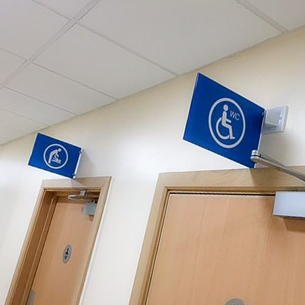 Double sided projecting sign giving directions to toilets