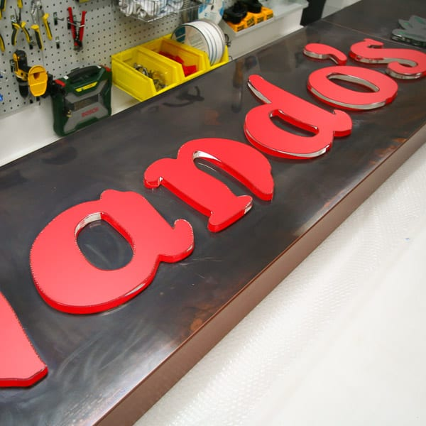 Nandos Restaurant sign being fabricated in our workshop. Made with an aged copper face with acrylic letters pushed through.