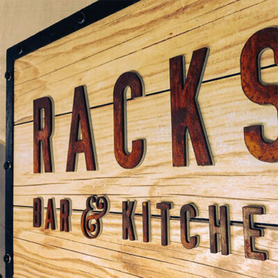 Restaurant signage utilising natural materials along with artificially aged materials