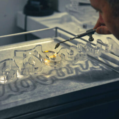 A skilled Voodoo employee flame polishing 20mm clear acrylic lettering