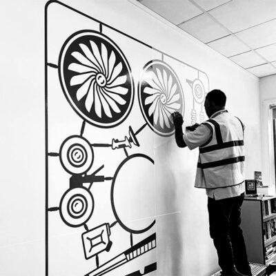 Large format custom stickers being applied to a wall
