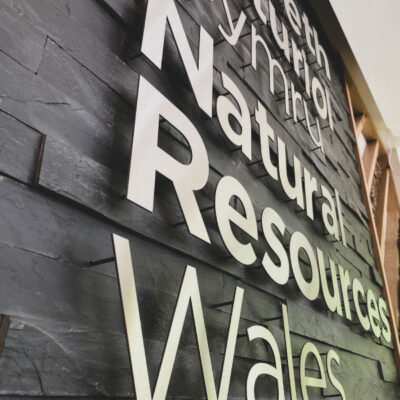 Metal letters mounted to a slate wall on stand off locators