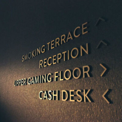 Metal letters pinned onto a textured wall in a casino